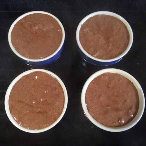 The puddings sitting in a water bath, about to go in the oven