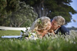Wedding Photography beach Bride and Groom kissing in the grass