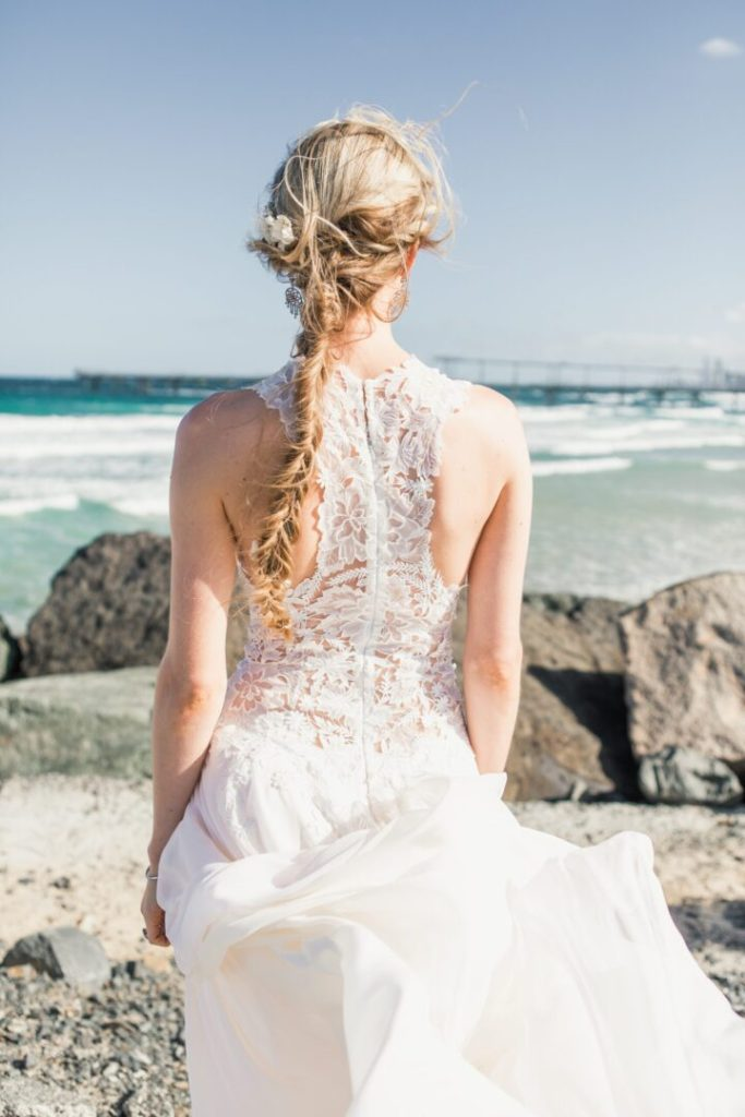 bride standing near ocean in wedding dress with long beautiful braided hair extensions