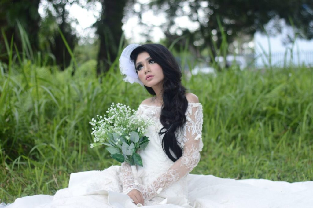 bride wearing white off shoulder bridal dress with long black hair-extensions flowing over her shoulder