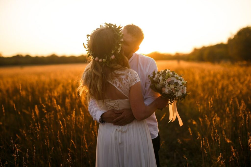 bride with wedding hair extensions standing in front of brown grass field kissing groom