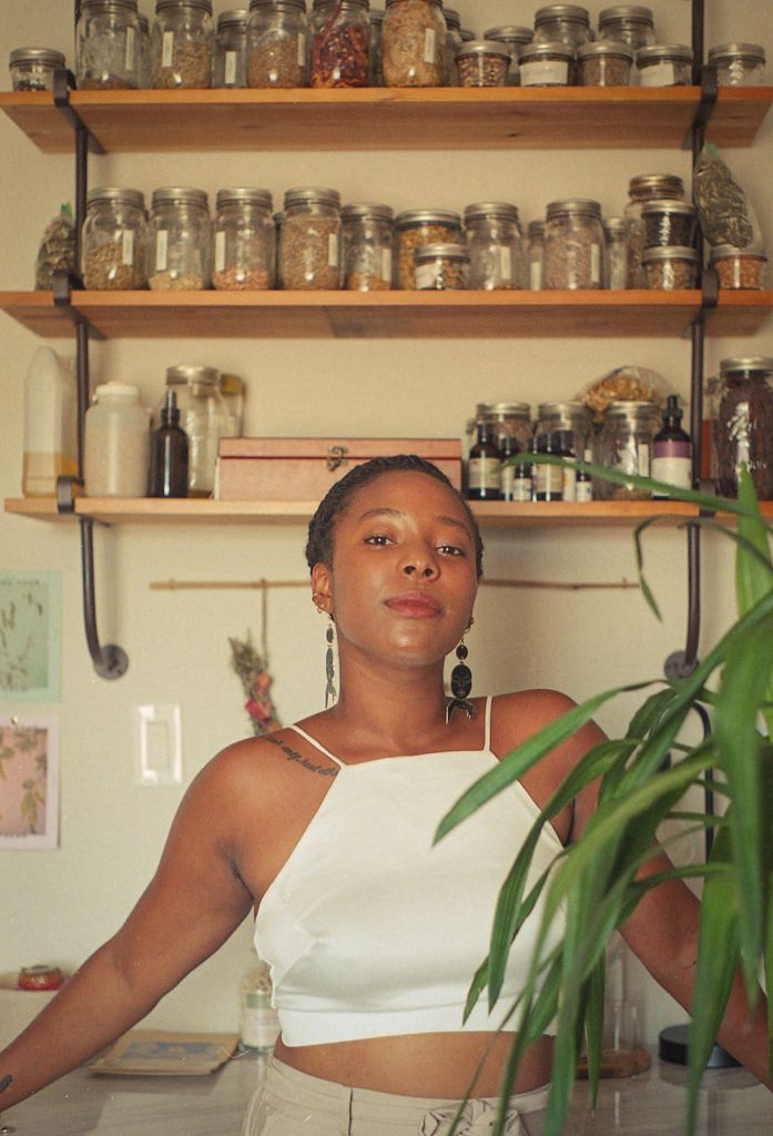 A brown-skinned black person with their hair braided back is looking straight ahead at you with an inviting look on their face. They are leaning back on a counter and their arms are extended out to the sides with their hands resting on the counter. There are shelves on the wall behind them filled with jars of herbs and bottles of oils. In front of them you can see a green plant peeking out, slightly blocking part of their left arm. The person is wearing a cropped white tank top and light beige pants. You can see a tattoo on the front of their right shoulder that wraps onto their collar bone. The tattoo is a string of text in black ink that's not readable. The person's chin is tilted slightly upward and they are wearing big dangly matching metal earrings with stacked shapes. The top part of the earring is a small flat circle, under that is a flat oval shape that has a face etched on it, and the bottom part of the earring is a line that's curved downwards like a rainbow.