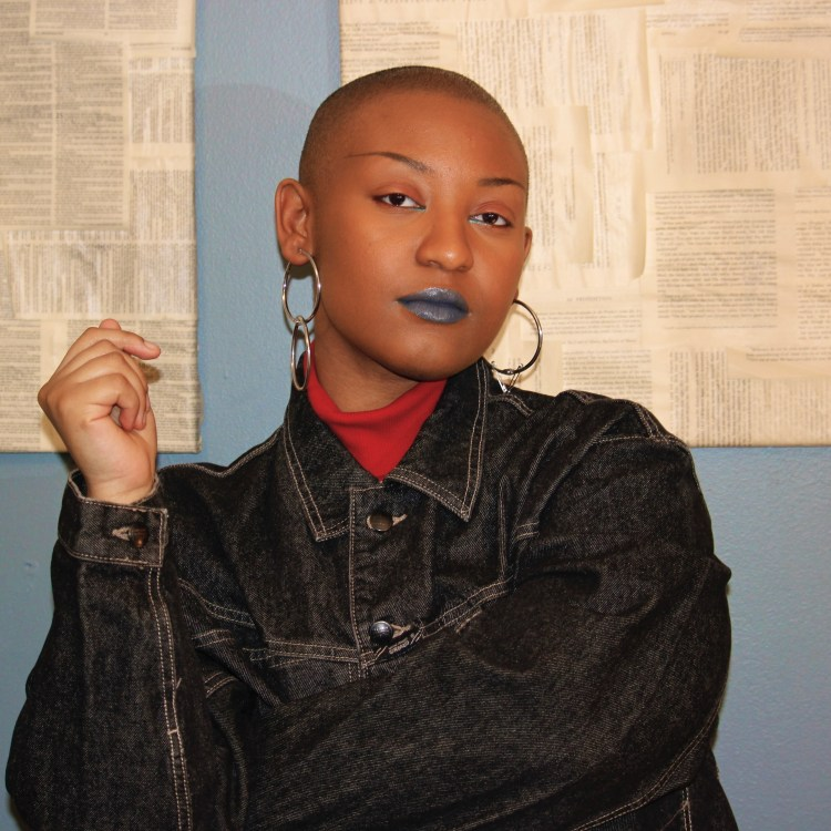 A brown-skinned Black person with a very short haircut is standing in front of a light blue wall that has two canvases on it covered in pages from a bible and the Qaran. The person has one arm folded against their chest with the arm folded up with their hand visible, in a relaxed pose. The person is wearing a red turtleneck under a very dark wash denim jacket. One of their earrings is two silver-colored circles linked together, while the other earring is one circle with two safety pins hanging from it. The person is wearing brownish-red eyeshadow on their top lid and on the outer lining of their under-eye. They are wearing a metallic blue eyeshadow on the inner corner of their eye. Their lipstick is a dark grey color with blue undertones.