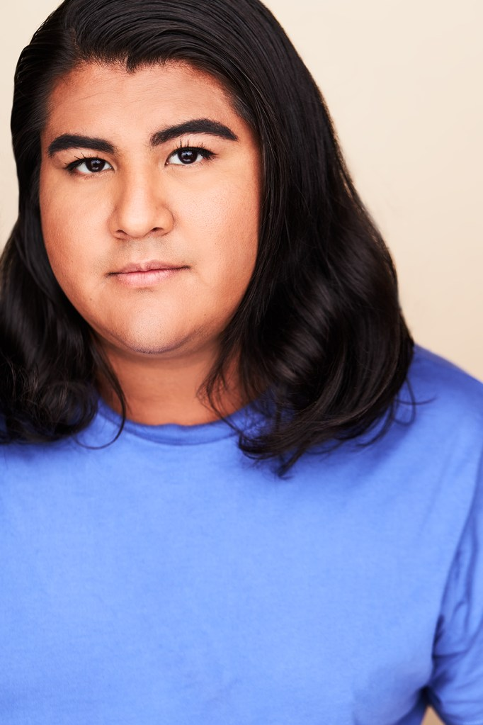 A brown-skinned nonbinary Mexican-American person is looking straight ahead with a neutral expression on their face. The person is at a close distance from you. They have long smooth black hair and dark brown eyes. They are wearing a light blue t-shirt and standing in front of a solid white background.