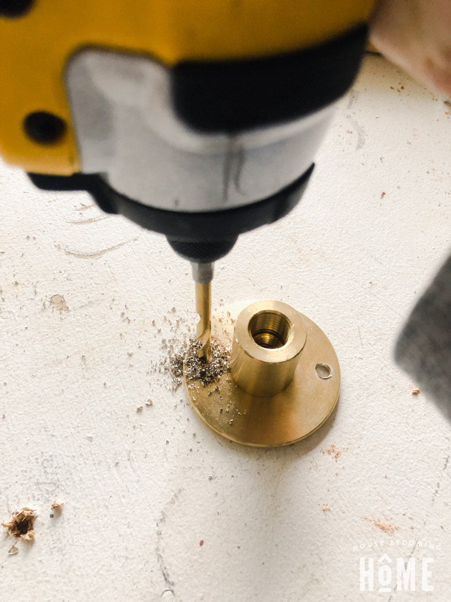 Make Holes in the Brass Flange to attach toilet paper holder to cabinet