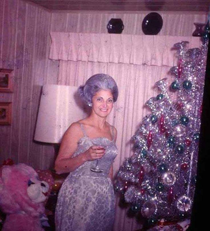women posing with their mid-century Christmas trees