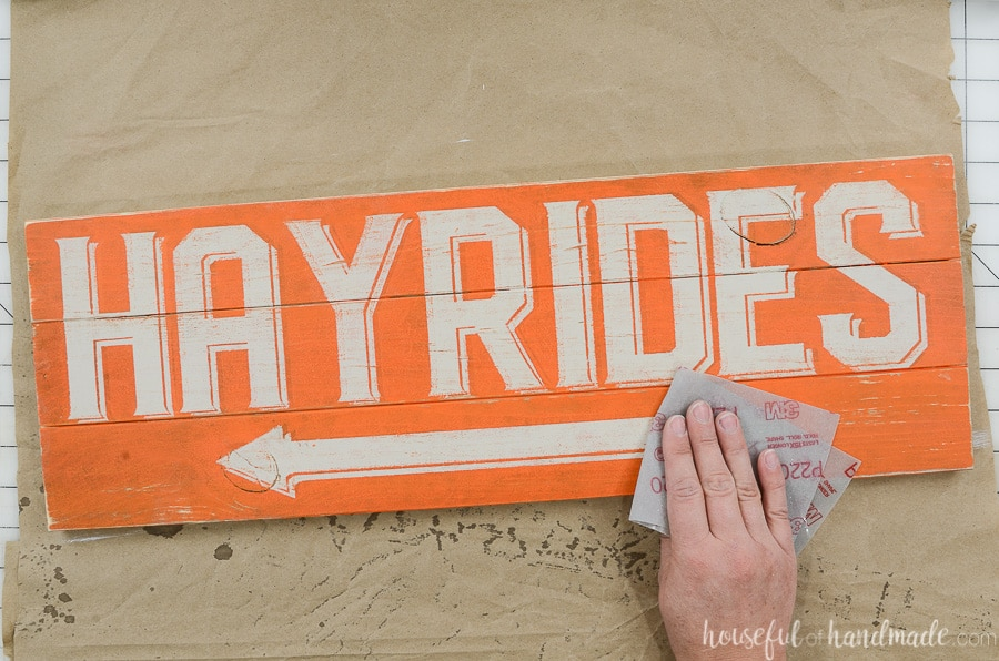 Sanding the hayrides side of the double sided sign by hand to give it a warn look.