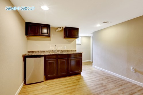 Empty basement room with dark brown kitchen cabinets. Mother-in-law apartment.