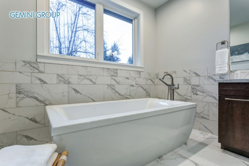 Incredible master bathroom with Carrara marble tile surround features a white freestanding bathtub over white and gray marble tile floor.
