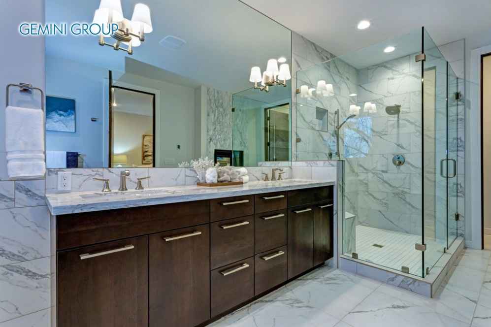 Incredible master bathroom with Carrara marble tile surround, modern glass walk in shower, espresso dual vanity cabinet and a freestanding bathtub.