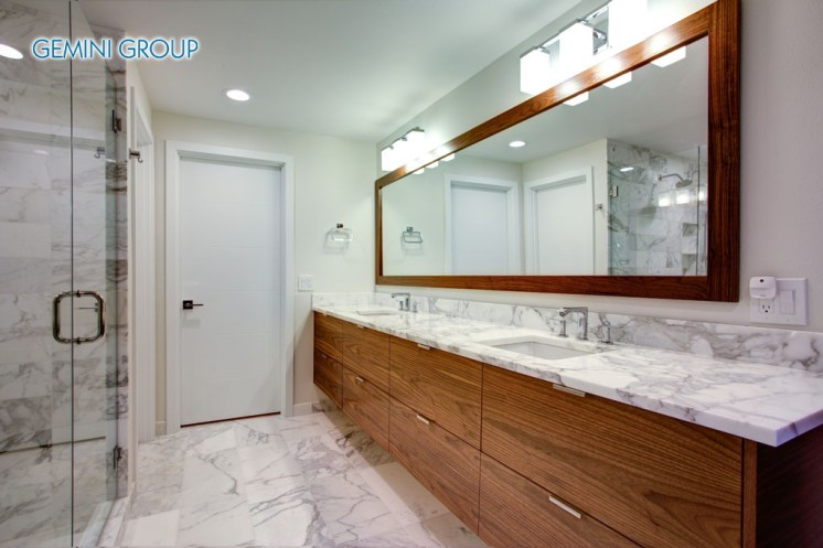 Sleek bathroom features double bathroom cabinet vanity with white gray marble countertop and white rectangle undermount sinks atop marble floor