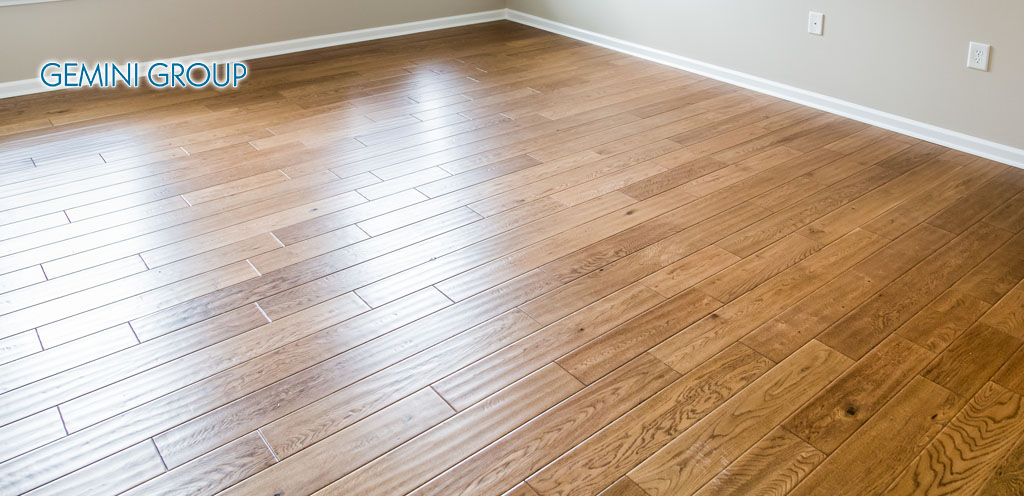 A shiny, polished hardwood floor in a new home