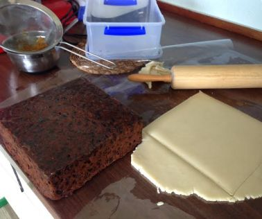 Cutting a square of almond paste to cover the top of the cake.