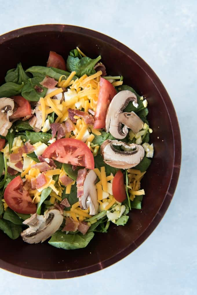 Spinach, Bacon & Egg Salad with Creamy Honey Mustard Dressing is perfect for a lunch or light dinner or to be served as a side salad. The sweet & salty combination of spinach, honey mustard, bacon, mushrooms, hard-boiled eggs, and cheddar cheese makes this one of my family's favorite salads ever!