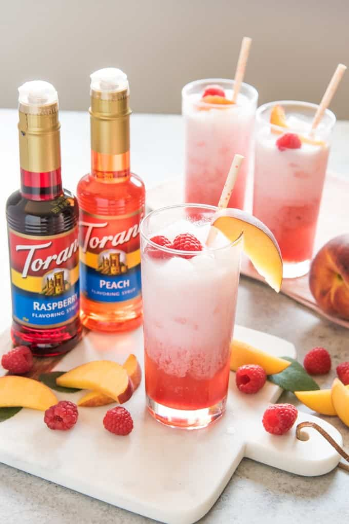 These easy and refreshing Raspberry Peach Italian Cream Sodas made with Torani syrups are the perfect non-alcoholic drink to serve all summer long!