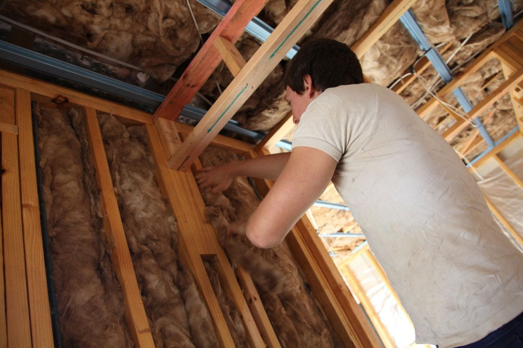 A man installing wool insulation into a home.