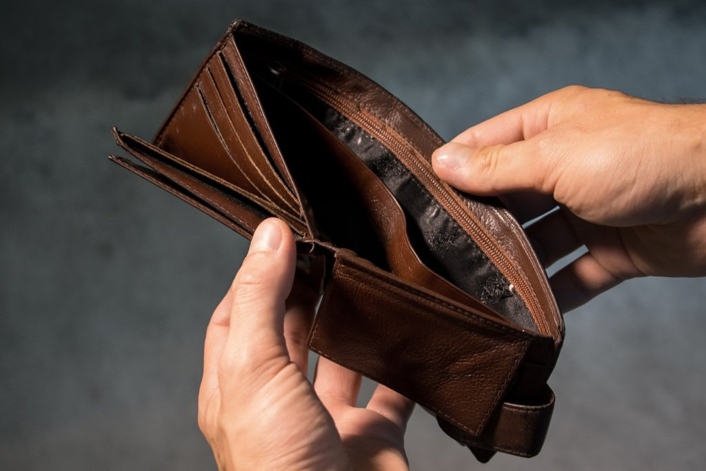 A man opening his empty wallet.