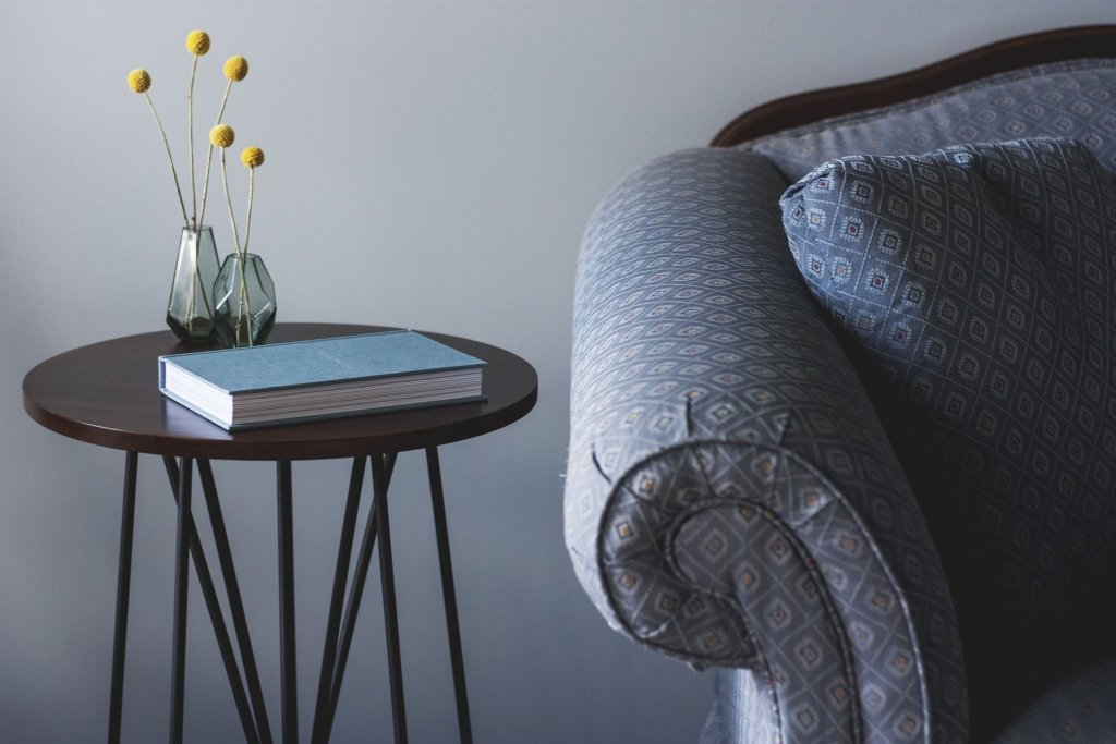 A blue chair next to a coffee table with a book and two small flower vases on it.