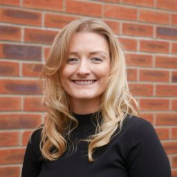 Eleanor Ogilvie, Women in Property's North West chair for 2021/22. She is smiling and standing against a brick wall.
