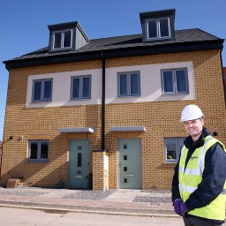 """Shaun Nixon, development contracts officer for Karbon Homes, on site outside a pair of """"Thetford"""" semi-detached, modular homes at the Central Park development in Darlington."""
