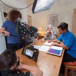 Four people sat around a dining table. Two of them are overseeing cameras and filming the other two.