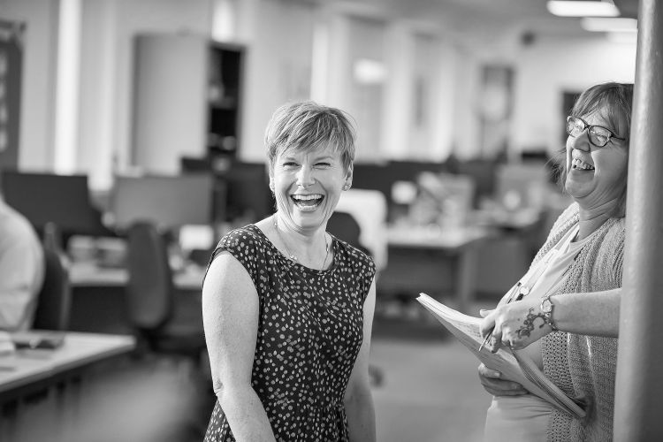 Two of Sovereign's female staff laughing in the office.