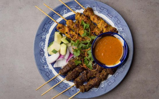 Round blue and white plate with chicken and beef skewers, vegetables, and orange/brown peanut sauce.