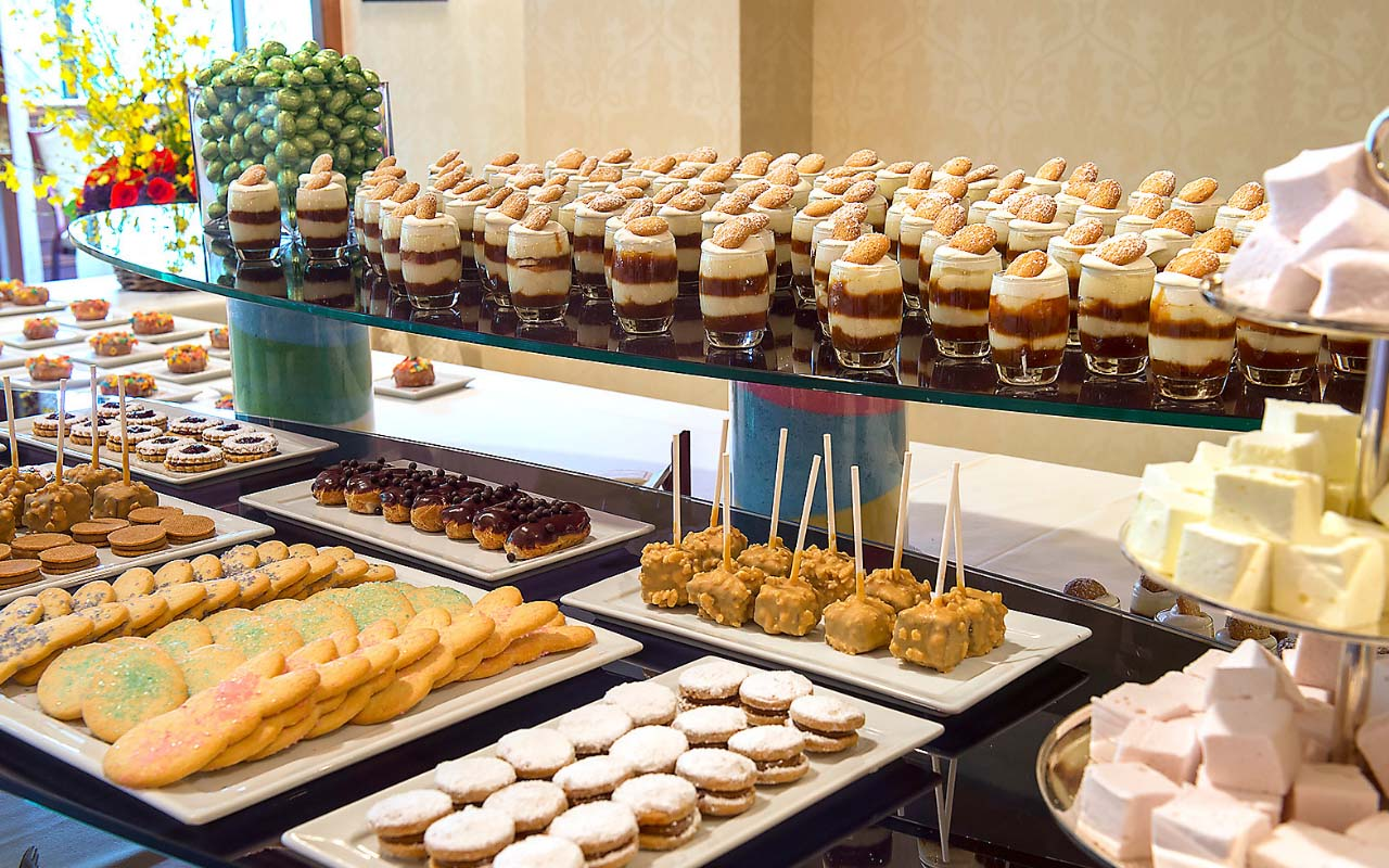 Large two-tiered table display of various petite desserts