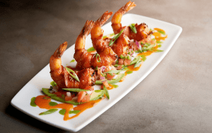 Rectangular plate with a line of four colorful bacon wrapped shrimp