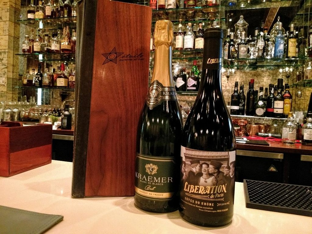 Photo of a bottle of sparkling wine and a bottle of the Liberation de Paris Cotes du Rhone on top of the bar at Etoile.