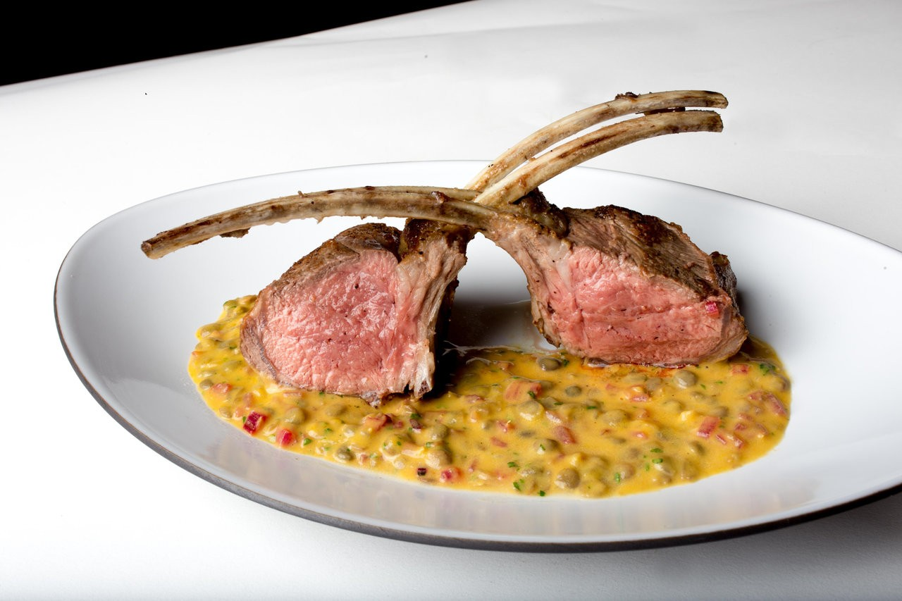 Photo of two lamb chops atop of a corn puree on a plate