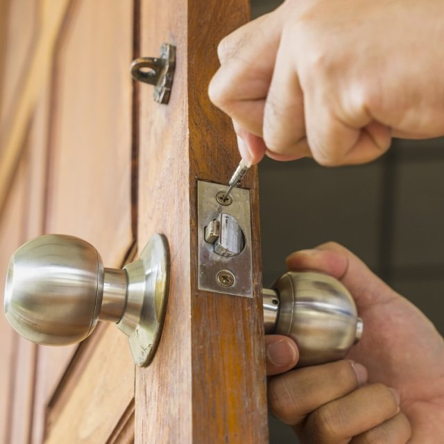 close-up hand holding lock knob on a brown door and second hand holding screwdriver on the latch of the lock