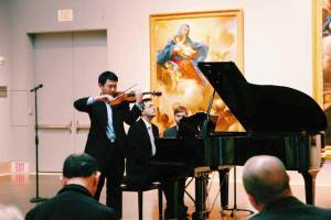 Violinist and pianist perform together.