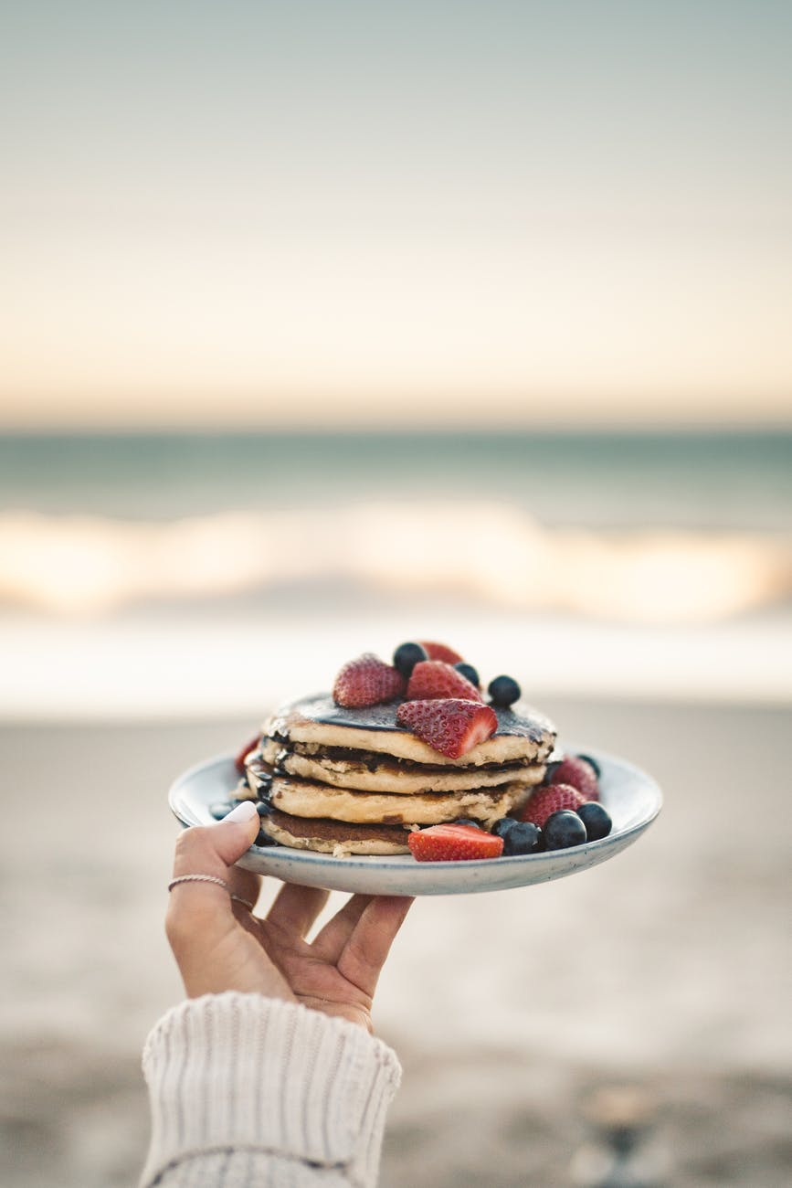 person holding plate of pancakes
