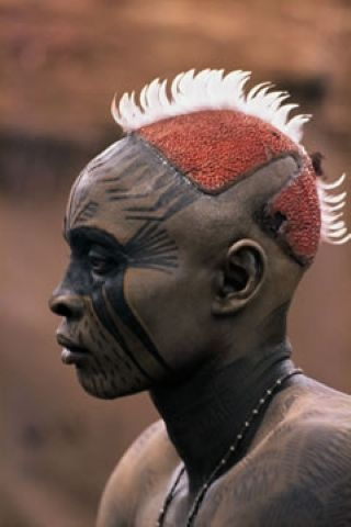Africa | A Nuba from Kau with his painted face mask.  Sudan.  Featured in the 19