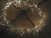 Great idea – 1 hula hoop (spray painted) + 2 strings of icicle lights and a bit