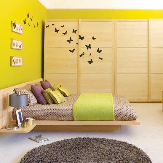 Yellow bedroom. I love the butterfly decals flying from the wardrobe to the wall