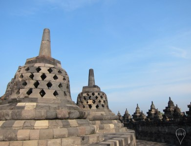 The top platform of Borobudur has three stages of stupas, including these with diamond-shaped lattice.