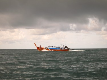 Longtail boat and rainclouds, more frequent during the low season