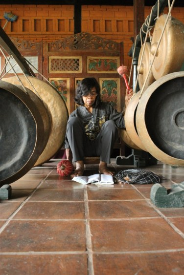A villager plays the gong in the gamelan