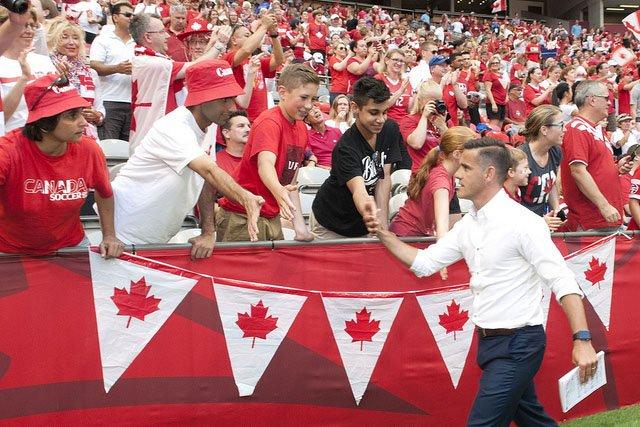 Coach John Herdman greets fans of the team