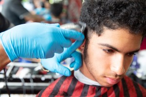 Hear Stories: a close-up picture of a young man getting a haircut from two hands wearing blue sanitary gloves.