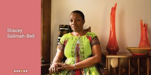 Meet Stacey Salimah-Bell, portrait of Bell sitting in her home, orange glass sculptures stand behind her.