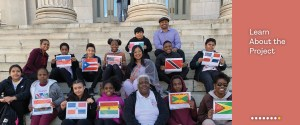 Learn about the project, a young student group sitting on the steps of Borough Hall holding up pictures of their nationality's flag.
