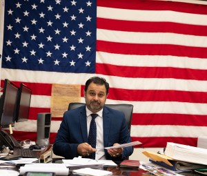 Meet the Narrators: A picture of Mohammad Razvi at his desk in front of an American flag.