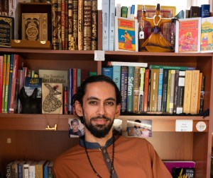 """""""Meet Asad Dandia"""" text graphic, portrait of Dandia in front of his library."""