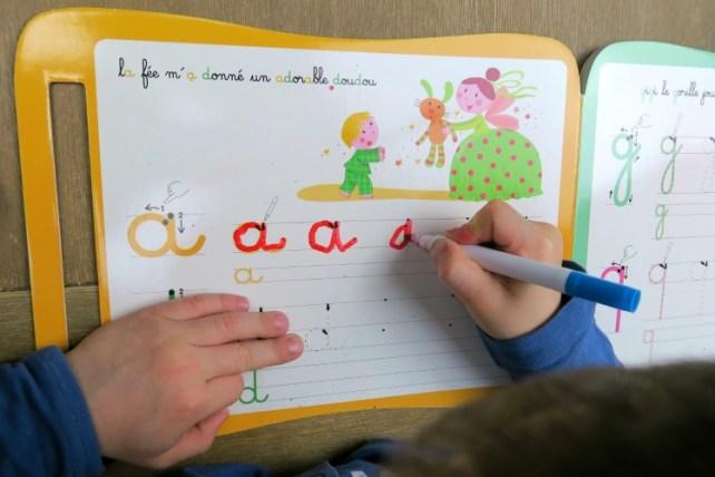 Atelier écriture lettres cursives sur livre ardoise