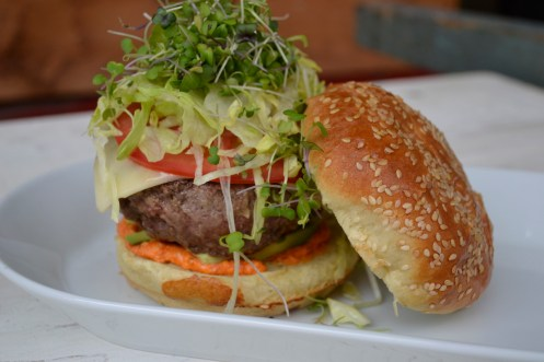 Burger with Chef Spreos' special sauce, cheese, tomato avocado, lettuce, and migrogreens.