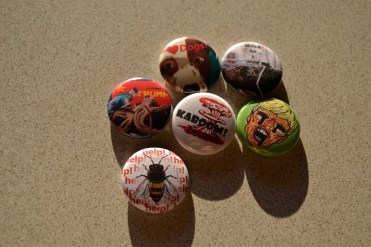 Packs of 6 randomly selected buttons are sold at Loading Dock Gallery.