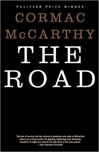 Cover of The Road by Cormac McCarthy. Cover is starkly plain: black with a white title and gold text.